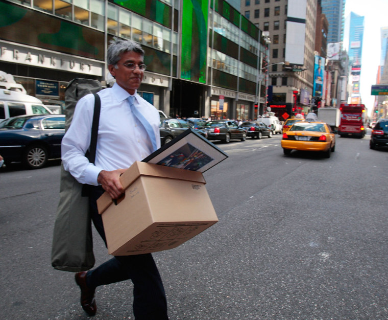 Image:  An employee of Lehman Brothers Holdings Inc. carries a box out of the company's headquarters