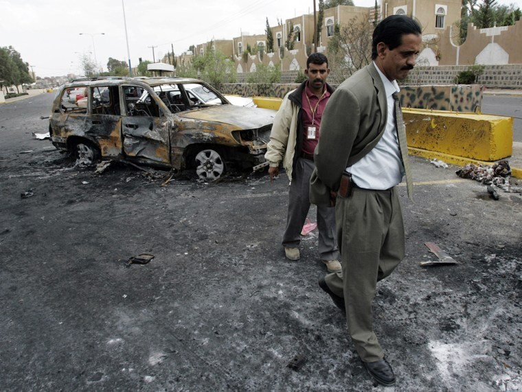 Image: Two US Embassy employees inspect damaged vehicles in front of the main entrance of the US Embassy in the capital San'a, Yemen