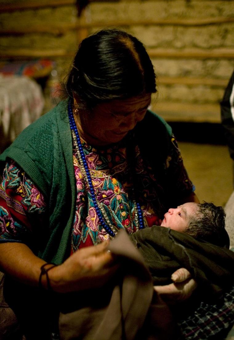 Image: Rural midwife Francisca Raquec, left, holds Sara Raquec's newborn son in El Llano