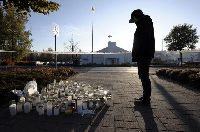 Image: A teenager looks at candles at dawn at the Kauhajoki vocational high school in Kauhajoki, southwestern Finland