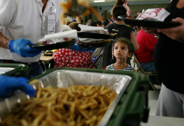 Hurricane Ike evacuee Nessa Devens, 4, of Corpus Christi, Texas, watches as a Red Cross volunteer serves dinner at a San Antonio Food Bank onSept. 11.
