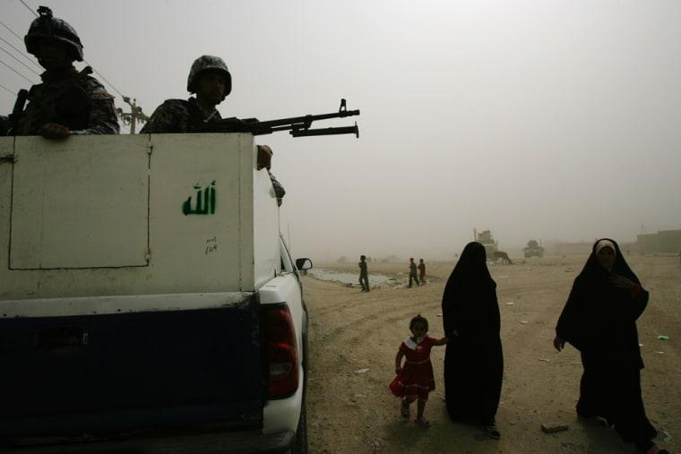 Image: Iraqi women walk past Iraqi soldiers