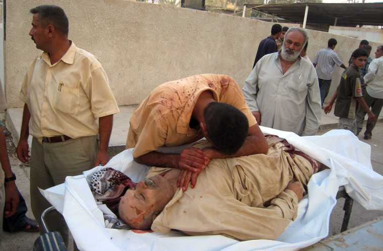 Image: A man weeps over the body of his relative as the bodies are brought to the morgue in the city of Baquba
