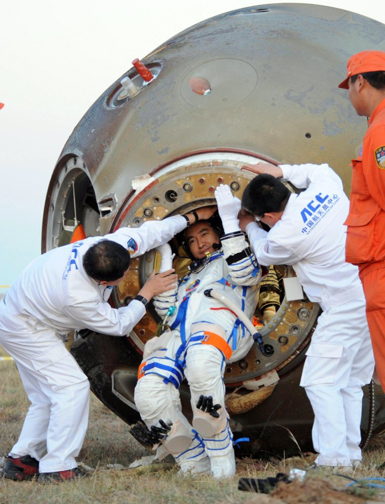 Image: Chinese taikonaut Zhai Zhigang is helped to get out of Shenzhou-7 re-entry module