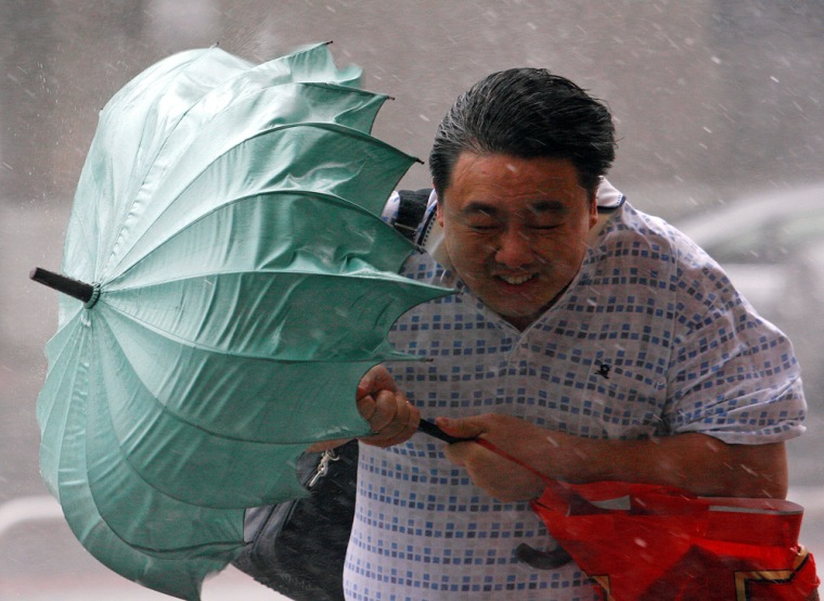 Image: Man struggles against wind with his umbrella as Typhoon Jangmi hits Taiwan