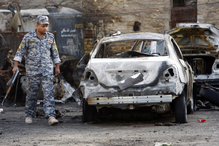 Image: A police officer looks at a burnt vehicle at a parking lot after a bomb attack in Baghdad