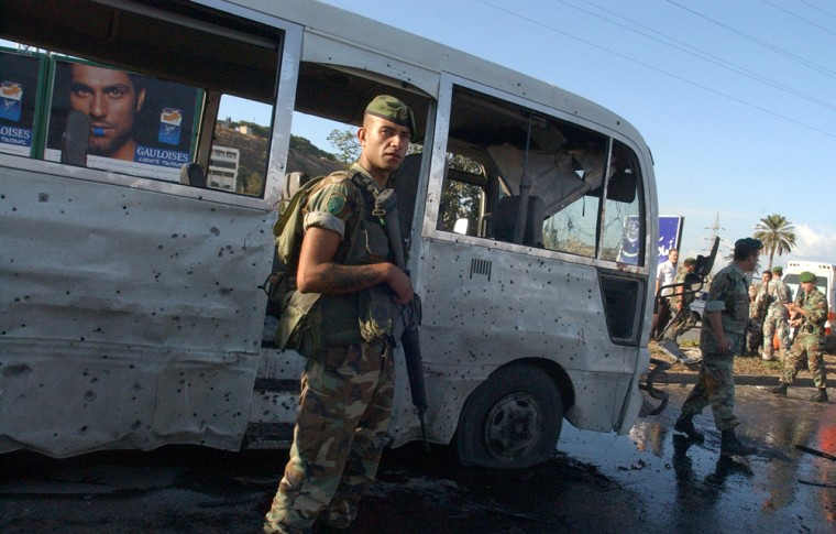 Image: Lebanese soldiers stand guard near a damaged bus
