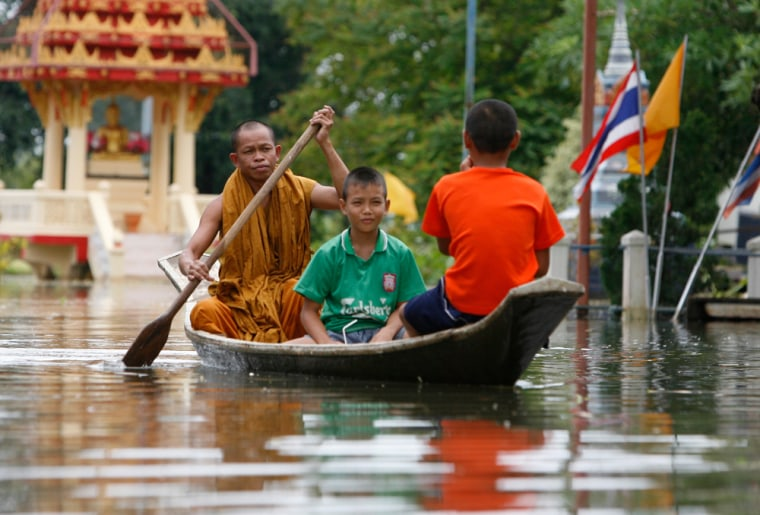 Image: A monk paddles a boat through flood waters at a temple in Thailand's Lopburi province
