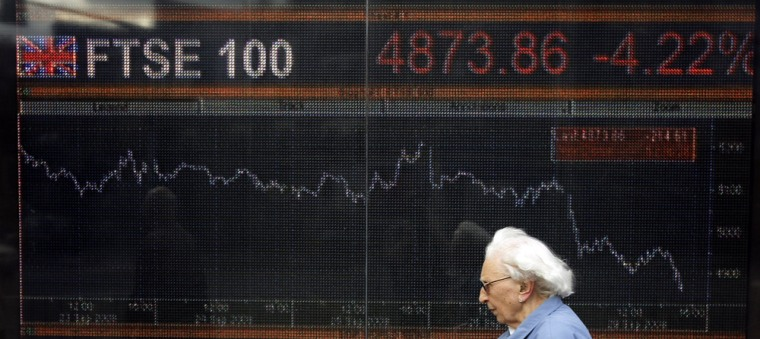 Image: A large screen graph shows the performance of Britain's FTSE 100 share index in London