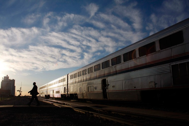 Image: An Amtrak train attendant walks across the tracks