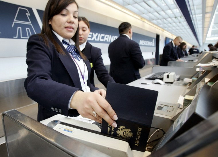 Image: An Mexicana Airlines agent checks a passsport