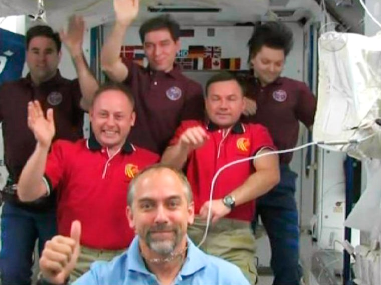 Image: Richard Garriott and the International Space Station crew members wave after crew news conference