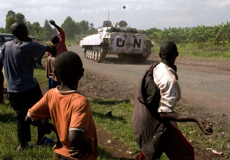 Image:People throw stones at UN peacekeepers patrolling on a road in Kibati