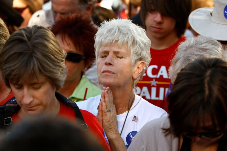 Image: A woman prays before the start of a rally with Republican presidential nominee Sen. John McCain