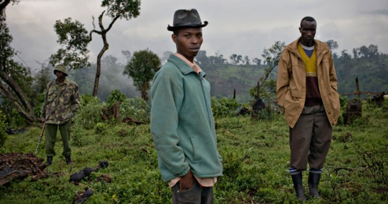 A Kenyan park ranger stands near residents who live on disputed land at the Mau forest
