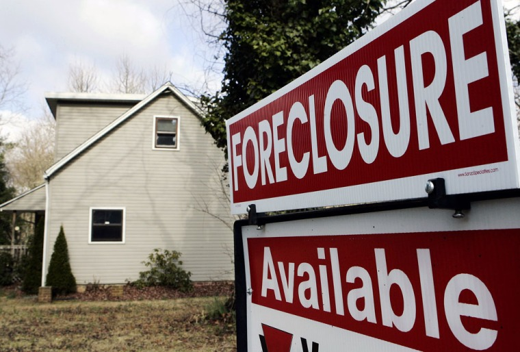 Image:  A realtor's sign is seen on the lawn of a foreclosed home