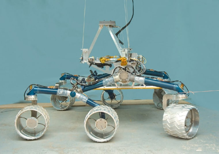 """NASA/JPL-Caltech     Facing Extinction The Mars Science Laboratory team's test rover \""""Scarecrow,\"""" is shown. The rover is named such because it's still missing its computer brain. Cost overruns and technical problems may delay or even cancel the NASA Mars rover project."""