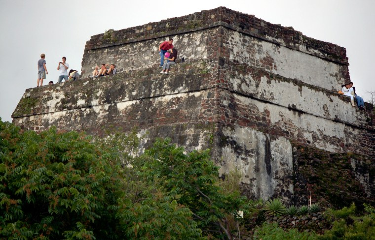 People relax atop the pyramid at the summit of the Tepozteco Hill, in Tepoztlan, Mexico. The 30-foot high pyramid dates back to the 12th century.