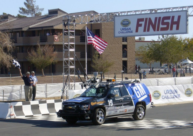 """""""Boss"""", a Chevrolet Tahoe SUV, heavily modified and robotized by a team of Carnegie Mellon university and General Motors, crosses the finish line at Saturday's DARPA Urban Challenge finals in Victorville, Calif. Boss was the second car to reach the finish line, behind Stanford's """"Junior,"""" but the Tartan Racing entrant won in part because of safety points."""