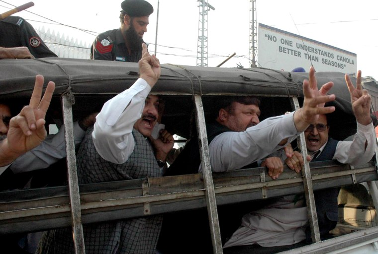 Leaders of a Pakistani opposition party makevictory signs Tuesdayfrom a police vehicle after their detention during a protest rally against President Pervez Musharraf's declaration of a state of emergency.