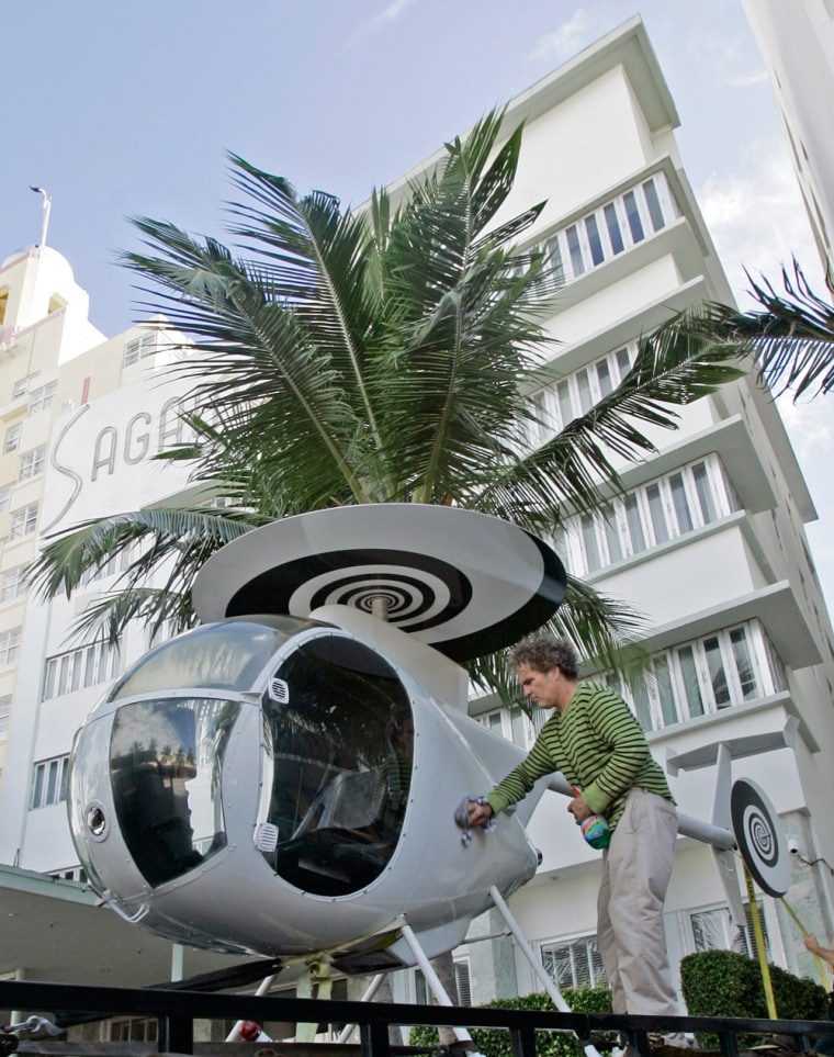 Artist Robert Chambers wipes his Rotorelief sculpture at its arrival at the Sagamore Hotel, where it will be permanently installed, in Miami Beach, Fla. The sculpture combines a functioning helicopter with hypnotic discs in place of propeller blades.