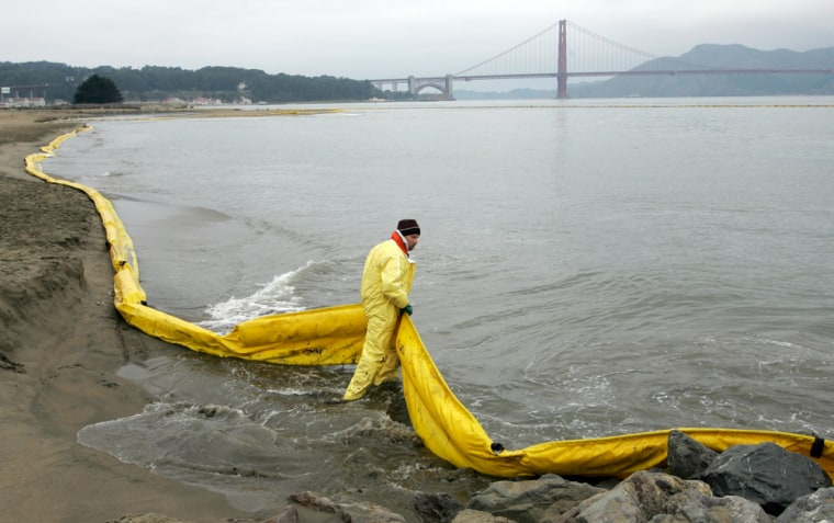 Hoping to keep oil off the beach, a cleanup worker positions a boom along the shore at San Francisco's Crissy Field on Thursday after the fuel oil spill in the bay. Behind him is the Golden Gate Bridge.