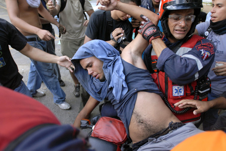 A paramedic carries an opponent of Venezuela's President Hugo Chavez who was injured by gunfire during clashes with Chavez supporters at Venezuela's Central University in Caracas onWednesday. Shots were fired during clashes where at least eight people were injured, including one by gunfire, officials said.