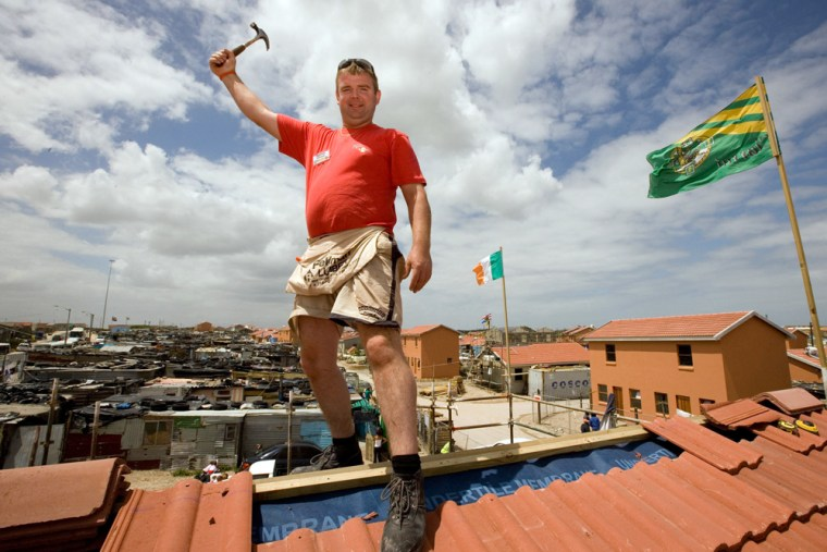 Image: Damian O'Driscoll poses for a photograph toward the end of a building blitz by nearly 1,400 Irish volunteers.