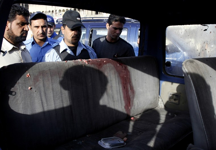 People gather to check the damage on a minibus hit by a roadside bomb Saturday in Baghdad.