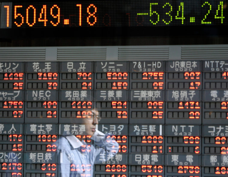 A pedestrian is reflected on a digital stock indicator in downtown Tokyo Monday. Asian markets fell sharply midday Monday as traders took their cues from Wall Street, where shares fell Friday amid renewed concerns about U.S. mortgage problems.
