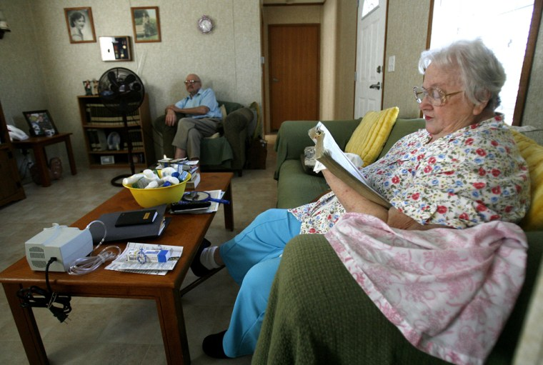 Daisy Carmouche reads the Bible on her couch where she spends most of her time since her medical condition deteriorated aftermoving into the FEMA-provided mobile home in Picayune, Miss.