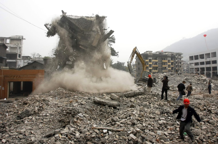 Workers blast an old building in Kaixian, southwest China, on Wednesday to make way for the Three Gorges Dam.