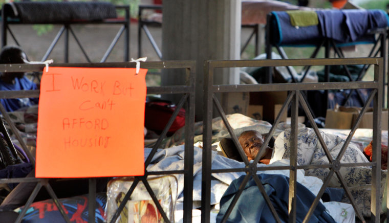 Image: A man sleeps in his bed under a gazebo at a homeless camp in a park across from City Hall in New Orleans