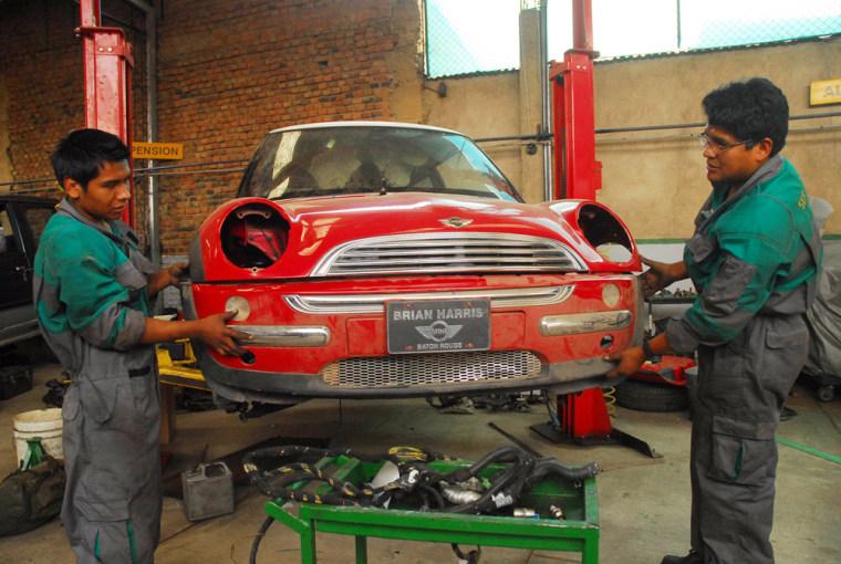 Images: Auto mechanics repair the red Mini Cooper.