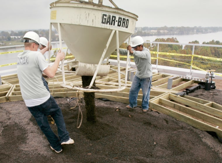 Image:  workers spread dirt on roof