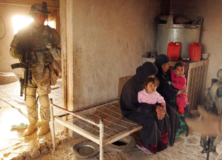Image: An Iraqi family waits on a bench as US soldiers search their home