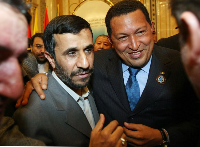 Image: Iranian President Mahmoud Ahmadinejad (L) stands with his Venezuelan counterpart Hugo Chavez