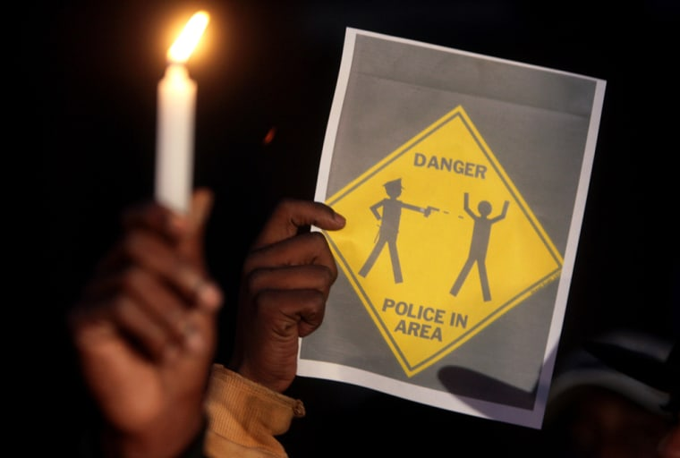 Image:  A warning sign is held up during a candlelight vigil