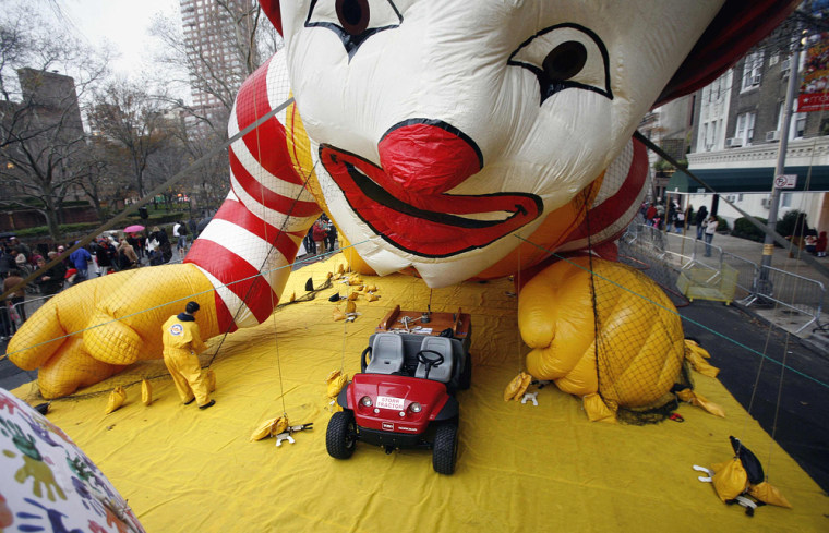 Image: A worker ties down a giant Ronald McDonald balloon after inflation for the Macy's Thanksgiving Day Parade in New York