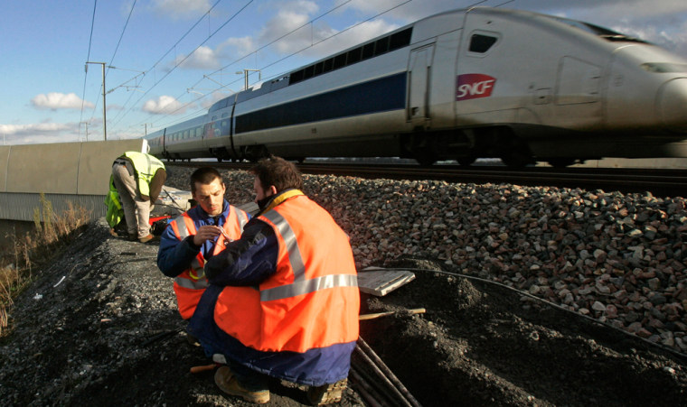 Railway workers replace a cable after an arson attack on the high-speed rail network inFrance further delayed passengers Wednesday.