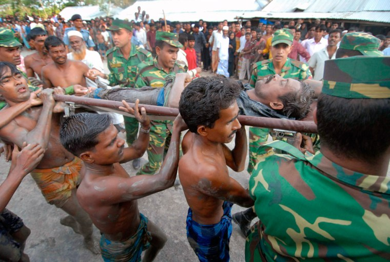 Image: Villagers and army soldiers carry an injured victim of a bridge collapse