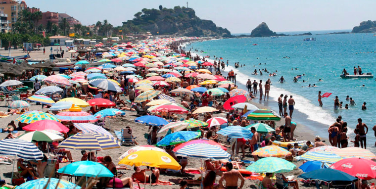 Image: Vacationers crowd the beach of San Cristobal in Almunecar