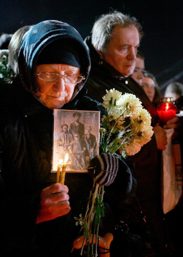 Image: An elderly Ukrainian woman holds a portrait of her family