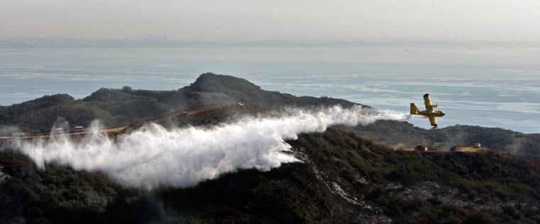 Image: A Super Scooper firefighting plane drops it load of water to put out hot spots in the hills above Malibu, Calif.
