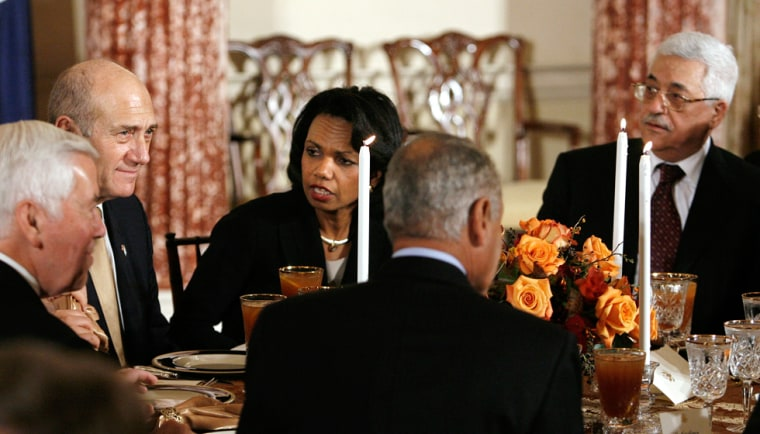 Image: US Secretary of State Rice sits between Israeli PM Olmert and Palestinian President Abbas during a dinner in Washington