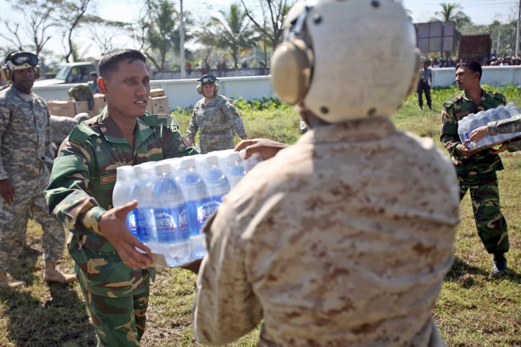 Image: U.S. Marine passes a Bangladeshi soldier a case of bottled water while unloading a shipment of food, water, and medical supplies