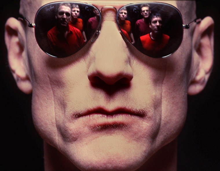 "Image: Australian rock band ""Midnight Oil"" reflected in the sunglasses of their lead singer Peter Garrett"