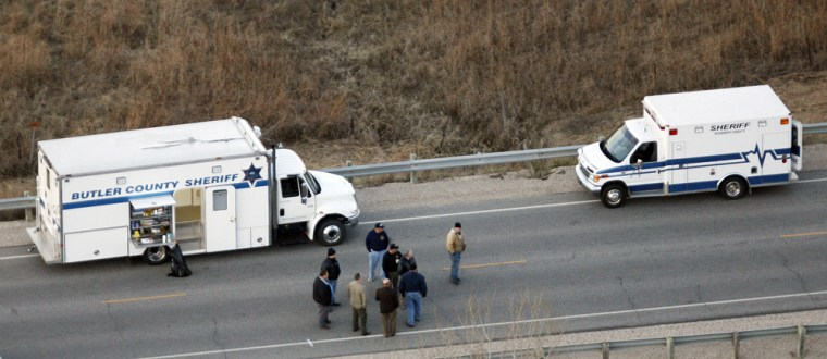 Law enforcement officials from Butler County stand on U.S. 54 near Toronto, Kan., on Thursday after finding a body that appears to be that of missing student Emily Sander.