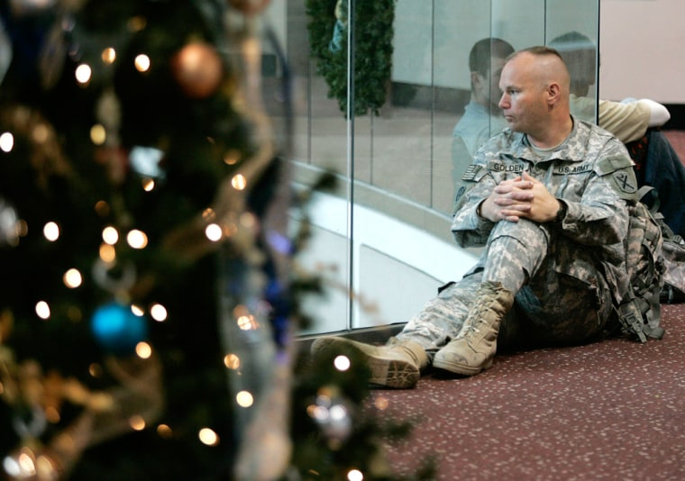 Image: Staff Sgt. Raymond Golden sits near a Christmas tree at the airport in Atlanta.