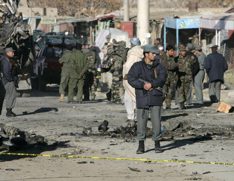 Afghan police officer stands guard at the site of a suicide car bomb blast in Kabul